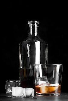 Стакан и бутылка с коктейлем со льдом
