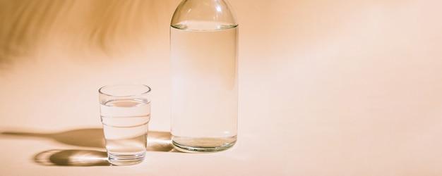 Стекло и бутылка с водой на пастели с тенью тропических пальмовых листьев