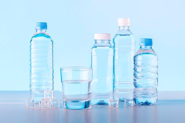 유리와 파란색 배경에 물 병입니다.