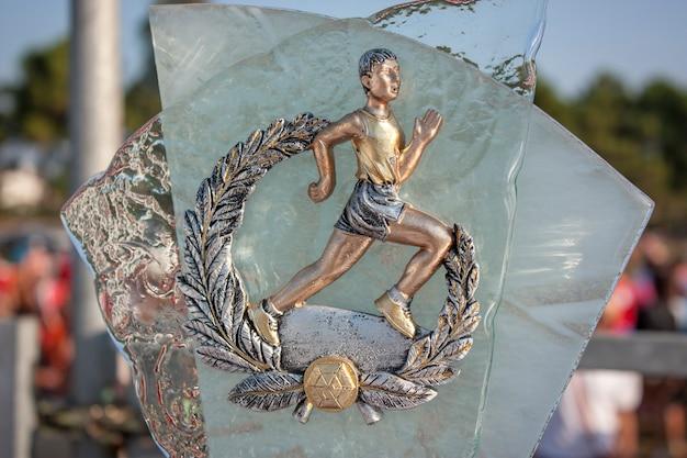 Стеклянный и металлический трофей за первое место в спортивном мероприятии по ходьбе, марафону, скачкам.