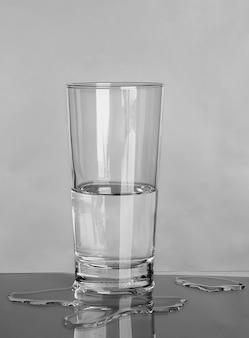 灰色の壁にガラスとこぼれた水