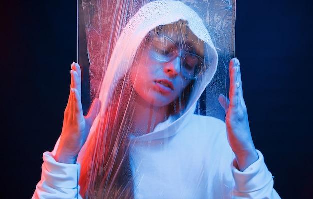 Стекло и вода. студия снята в темной студии с неоновым светом. портрет молодой девушки.