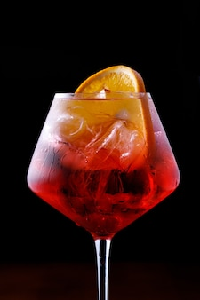 Glass of aperol spritz cocktail on a black background close up.