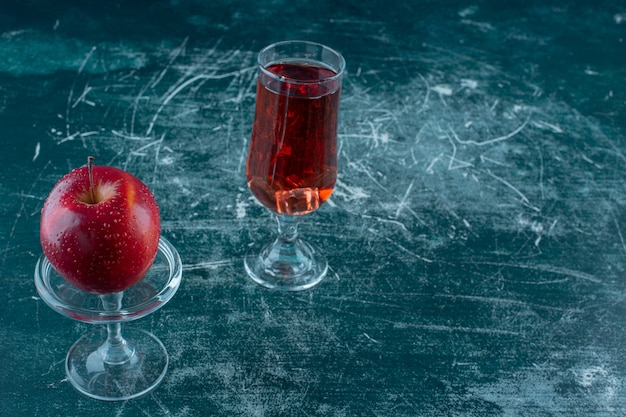 Un bicchiere di succo di mela e mela sul piedistallo, sul tavolo di marmo.