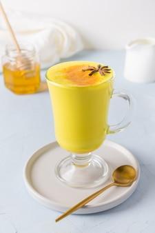 Glass of ayurvedic golden turmeric latte milk with honey, curcuma powder on white.
