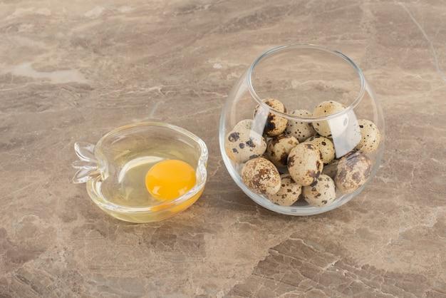 메추라기 알의 유리 볼과 날달걀의 접시.
