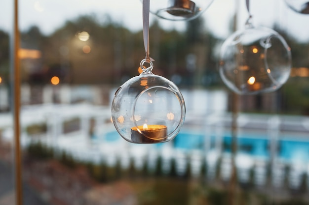 Glass balls with candles hang before the window