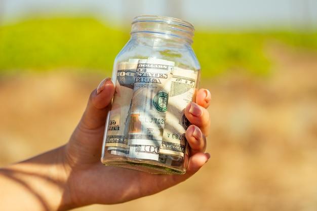 Стеклянный банк с купюрами (деньгами) в руках на зеленом фоне