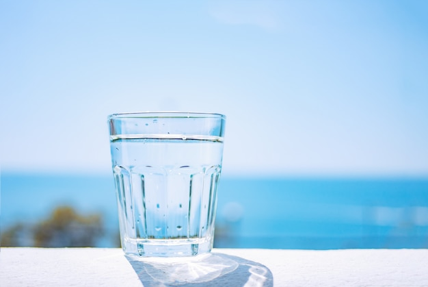 A glass beaker filled with clear water stands on a sandy beach by the sea. healthy lifestyle.