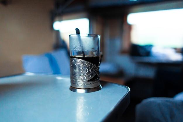 Стакан стеклянный в металлическом держателе. визитная карточка железной дороги. путешествие поездом.