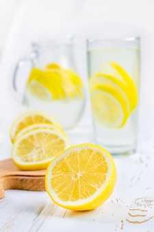 A glass beaker and a jug of cold lemonade on a white wooden background surrounded by lemons.