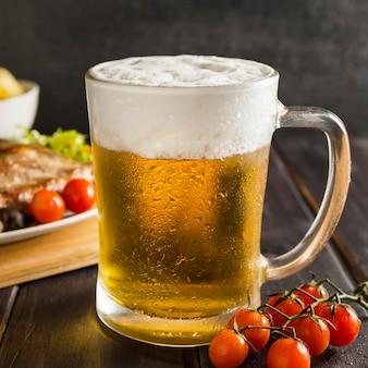 Bicchiere di orso con bistecca e pomodori