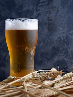 A glass of beer against a dark wall