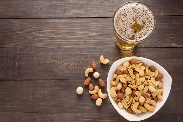 Glass of beer and almond, macadamia, peanut, cashew nut on the wooden background