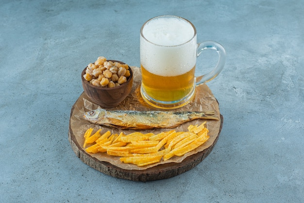 A glass of beer and appetizers on board, on the blue table.