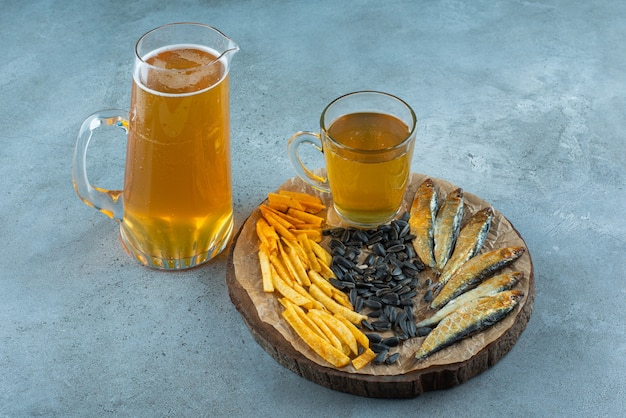 A glass of beer and appetizers on board and a jug of beer, on the blue table.