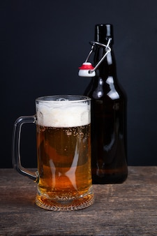 Glass of beer and beer bottle on a black