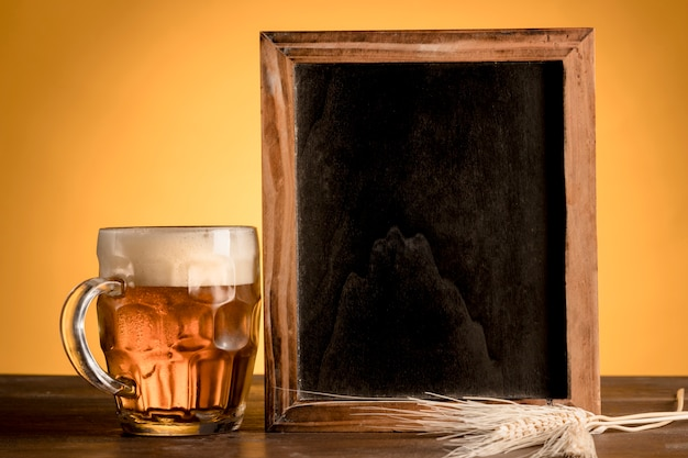 Glass of beer and blackboard on wooden table