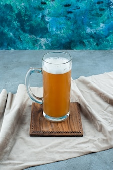 A glass of beer on a board on a towel, on the blue table.