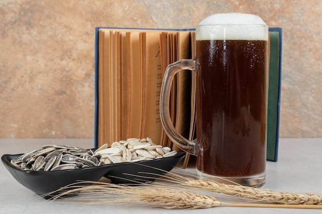 Bicchiere di birra, libro e piatto di semi di girasole
