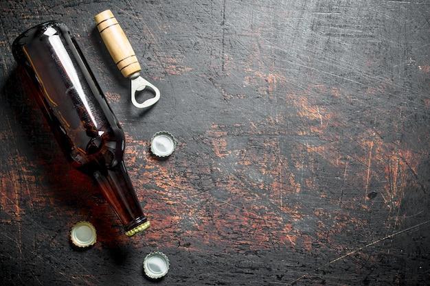 Стеклянная пивная бутылка и открывалка. на темном деревенском фоне