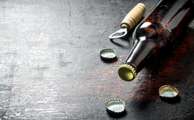 유리 맥주 병 및 오프너. 어두운 시골 풍 테이블에