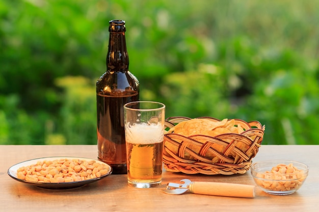 Glass of beer and bottle of beer on wooden table with potato chips in wicker basket, peanuts in plate and bowl in natural green blurred background