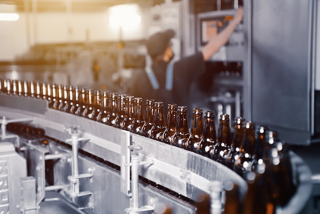 Glass beer bottles of brown color on the conveyor line
