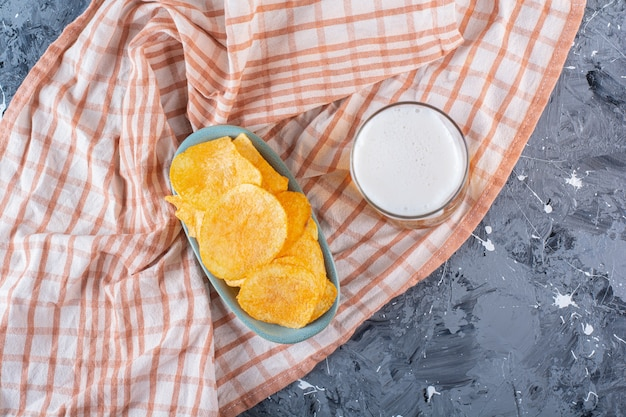A glass of beer and bowl of chips on tea towel , on the marble surface