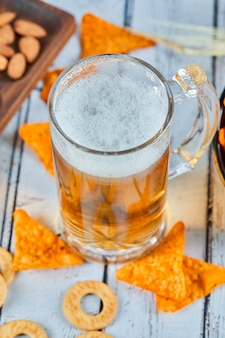 A glass of beer and chips on blue table, close up.