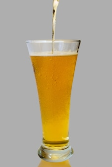 Glass of beer close-up with froth over grey