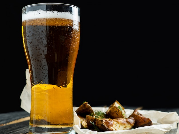 Glass of beer and country style potatoes with dill on dark background
