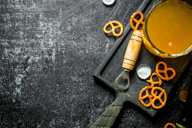 Glass of beer on a cutting board with snacks and opener. on black rustic background
