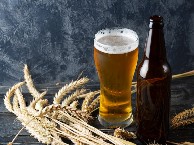Glass of beer on a dark stone with beer bottle and wheat copy space