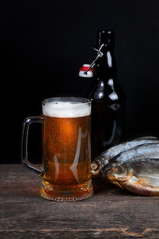 Glass of beer, dry fish and beer bottle on a black