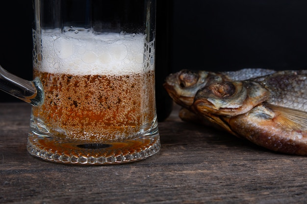 Glass of beer and dry fishon a wooden table