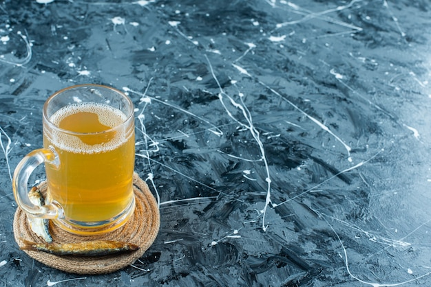 A glass beer and fish on trivet on blue.