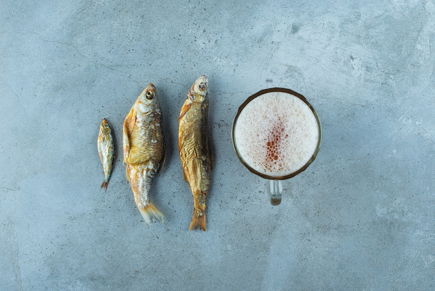 A glass beer of next to fishes, on the blue table.
