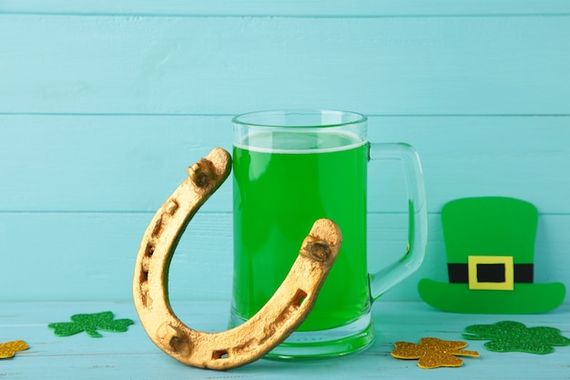 Glass of beer and horseshoe for st patricks day on blue background. top view