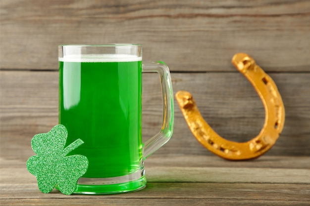 Glass of beer and horseshoe for st patricks day on grey wall. top view.