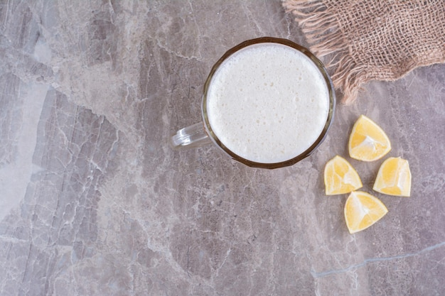 Glass of beer and lemon slices on marble surface. high quality photo