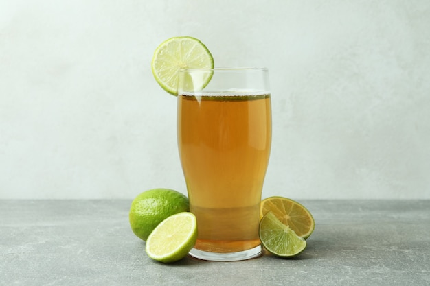 Glass of beer and limes against white textured background
