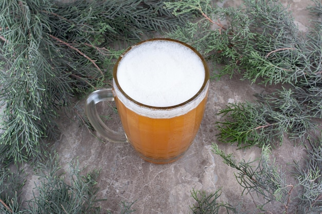 Glass of beer on marble surface with pine branch