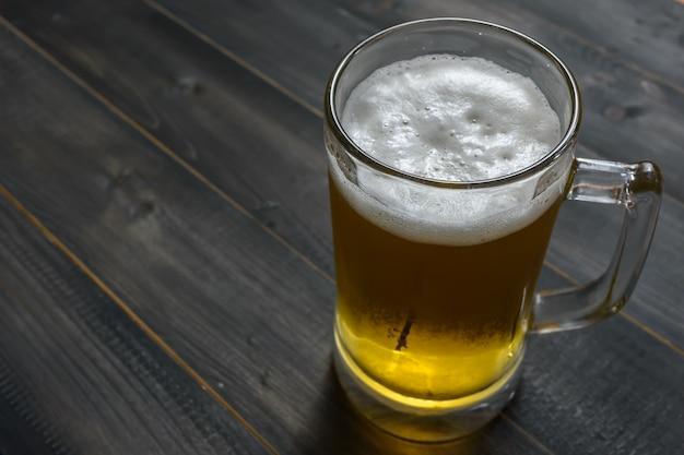 コピースペースと木製の背景にガラスビール