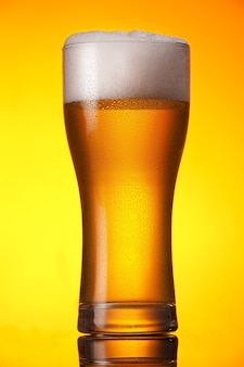 Glass of beer over orange background