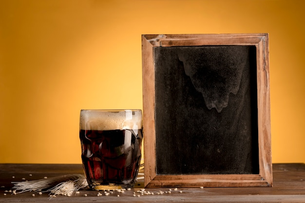 Glass of beer putting next of blackboard on wooden table