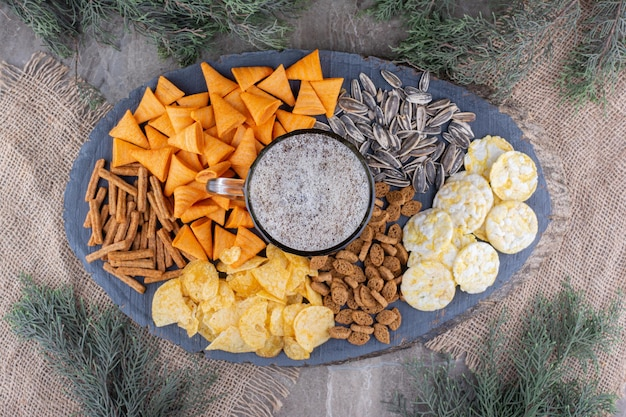 Glass of beer and snacks on wooden piece. high quality photo