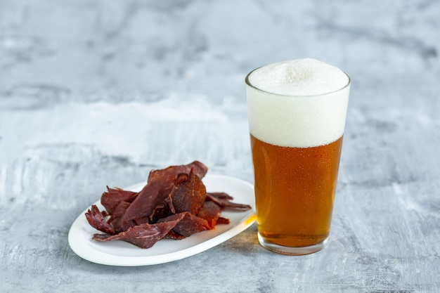 Glass of beer on the stone table and bricks surface