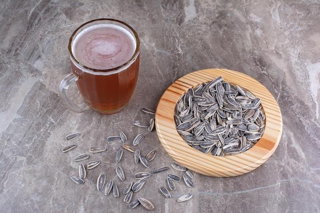 Bicchiere di birra e semi di girasole sul tavolo di marmo. foto di alta qualità