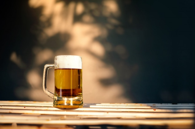 A glass of beer on table in summer sunny day. shadow of tree